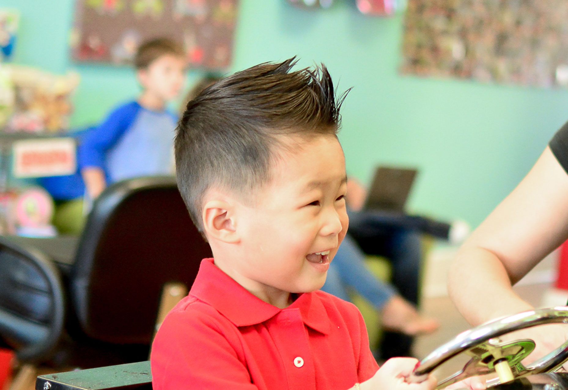 LIttle asian boy smiling after a great haircut